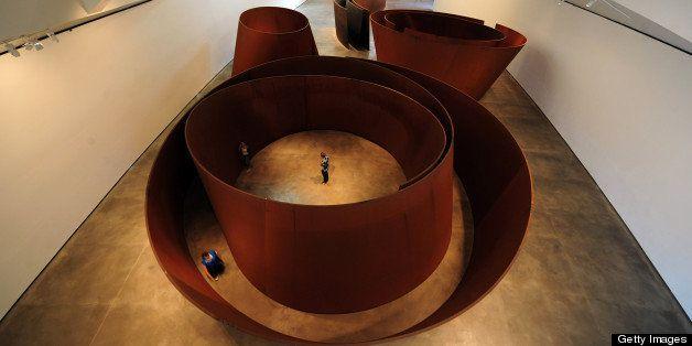 People walk among US artist Richard Serra's sculptures 'The Matter of Time', during the presentation of the Guggenheim Bilbao