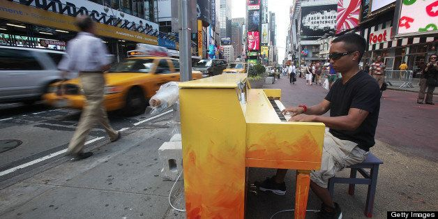NEW YORK - JUNE 21:  Allan Decipulo play a piano in Times Square as part of the 'Play Me, I?m Yours' public art installation