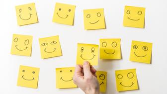 Yellow sticky notes on whiteboard. The notes have smiles drawn with a black color marker to represent the happy clients