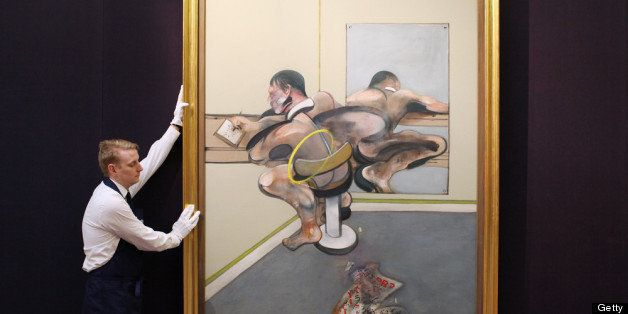 LONDON, ENGLAND - APRIL 12:  A gallery technician at Sotheby's auction house adjusts a painting by Francis Bacon entitled 'Fi