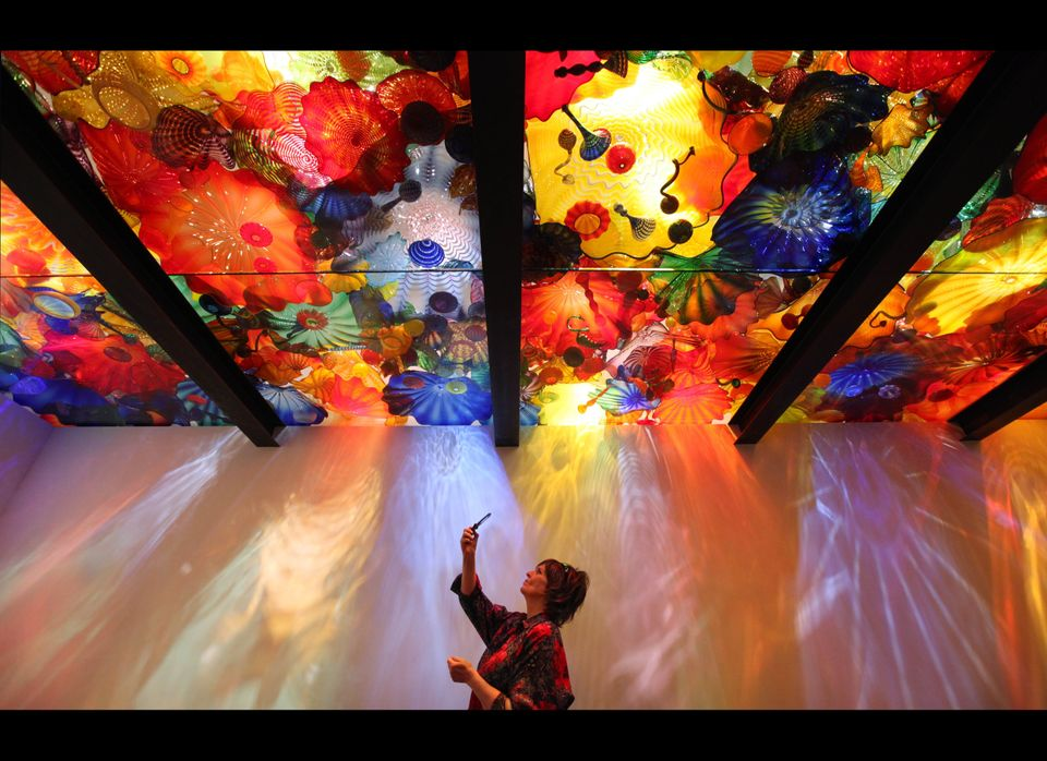 """Kay Solberg takes photos of the """"Persian Ceiling"""" during a preview of the Chihuly Garden and Glass exhibit at the Seattle Cen"""