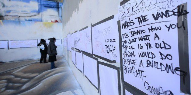 People write messages at New York's graffiti iconic spot '5Pointz' as it stands defaced with white paint covering most of the