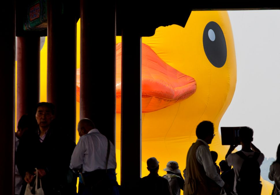 Visitors in a traditional pavilion take photos of a giant yellow rubber duck created by Dutch artist Florentijn Hofman floati
