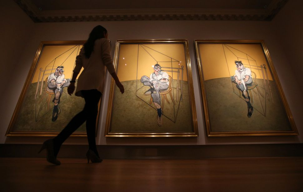"""A member of Christie's staff walks towards Francis Bacon's """"Three Studies of Lucien Freud."""" The work became the most expensiv"""
