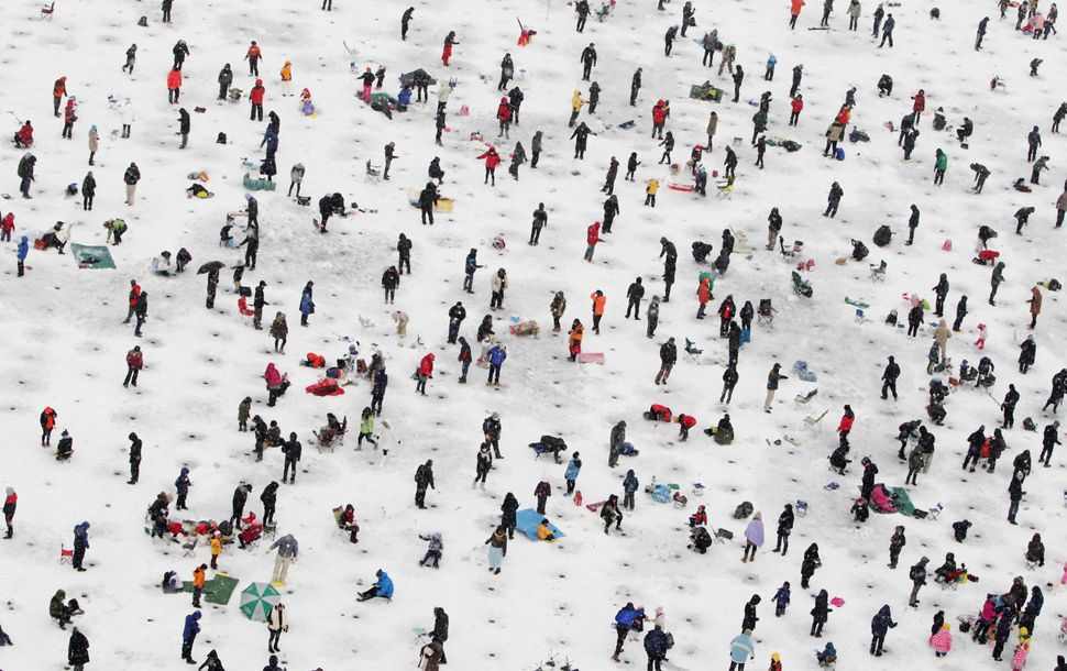 Anglers cast lines through holes into a frozen river during an ice fishing competition at the Hwacheon Sancheoneo Ice Festiva
