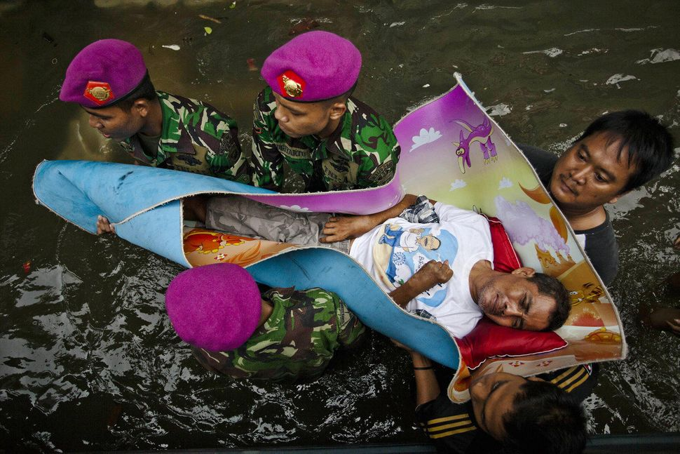 Local resident Syamsuri is evacuated by Indonesian Army as major floods hit North Jakarta on January 20, 2013 in Jakarta, Ind