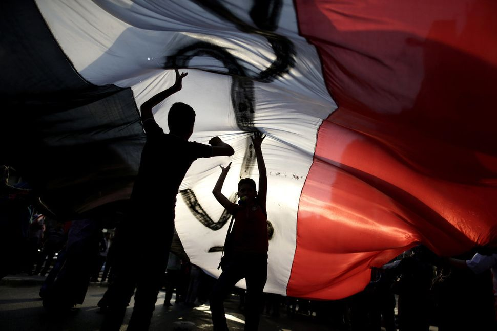 Opponents of Egypt's Islamist President Mohammed Morsi hold a large Egyptian national flag during a protest outside the presi
