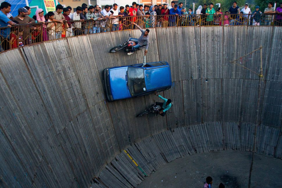 Stunt driver and motorcyclists  perform in the well of death on June 20, 2013 in  Srinagar, the summer capital of Indian admi