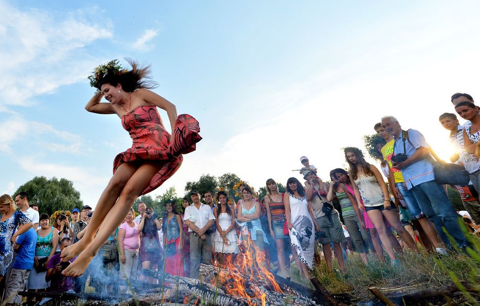 A girl jumps over a campfire while celebrating Ivan Kupala Night, a traditional Slavic holiday not far from Kiev on July 6, 2