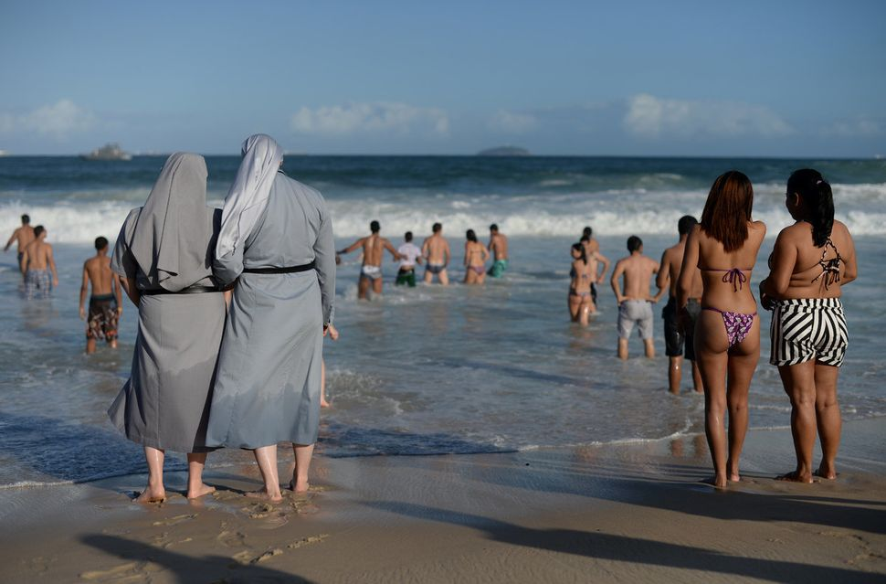 Two Polish nuns look at people bathing as hundreds of thousands of young Catholic pilgrims attending World Youth Day (WYD) st