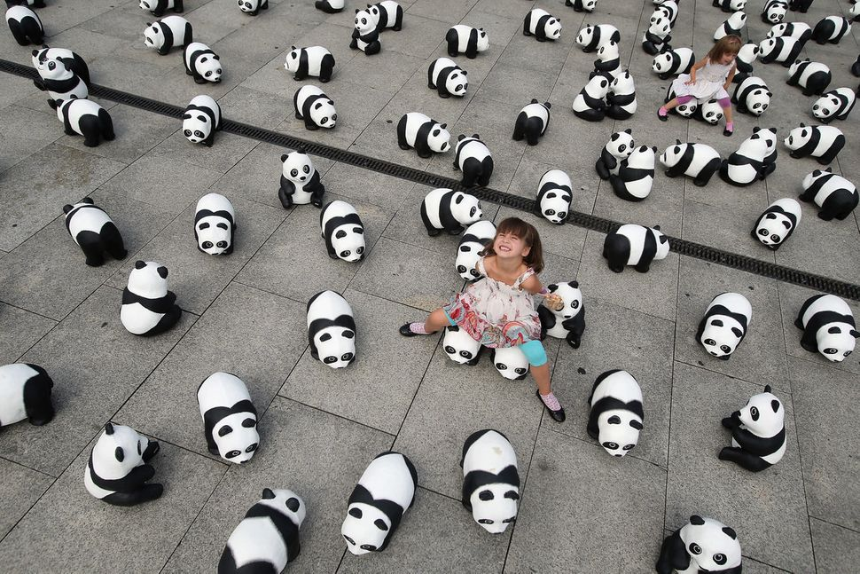 Elaia (C), 6, and her sister Lusitta, 4, play among 1,600 styrofoam panda bear sculptures displayed in front of Hauptbahnhof