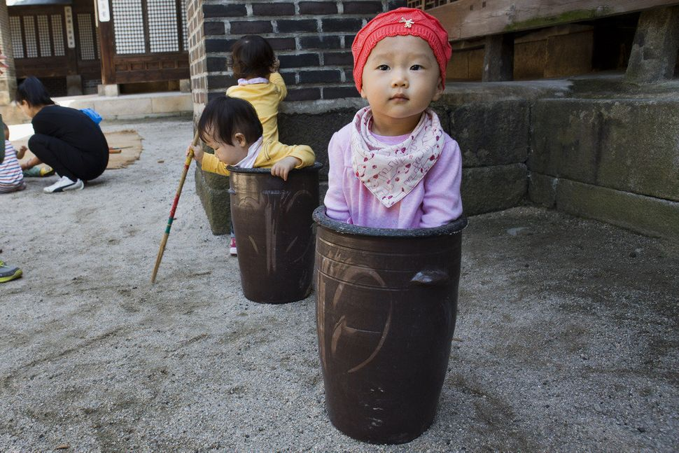 Jung Ha-yoon, 2, appears to be stuck inside a ceramic container while playing with other children at the traditional sports s