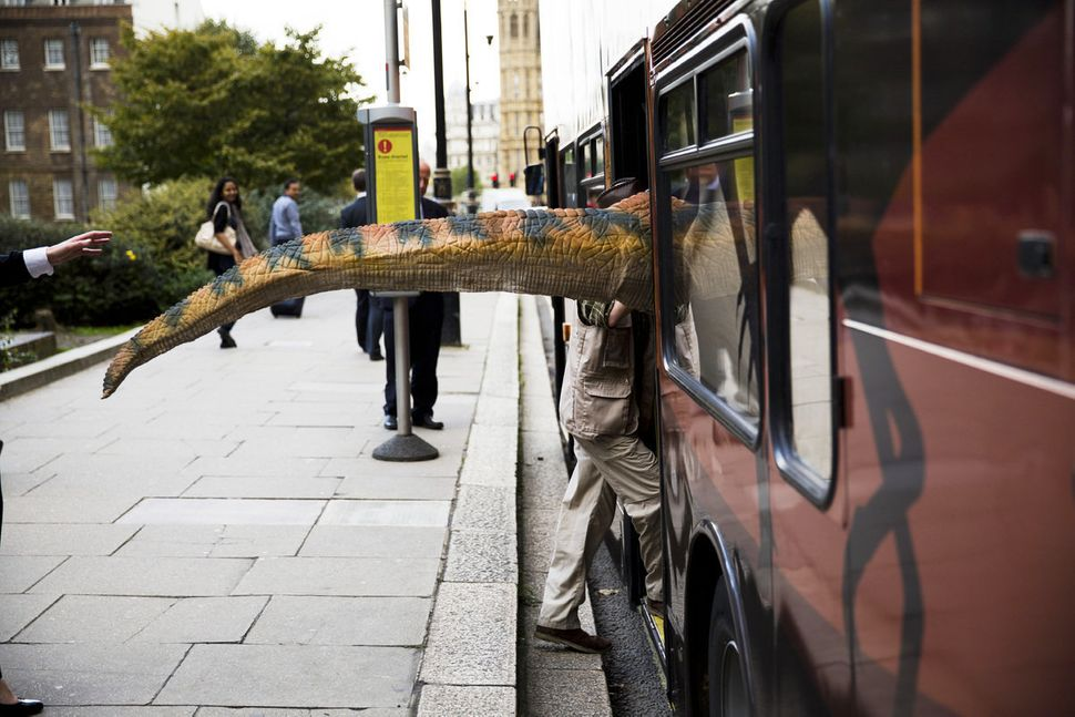 The tail of a dinosaur costume sticks out as the person wearing it boards a bus they had to promote their exhibit, near the H