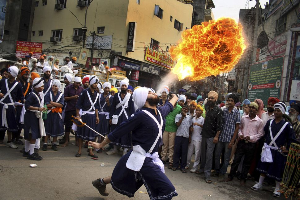 A Sikh youth performs an act of fire as he displays martial art skills during a religious procession on the eve of birth anni