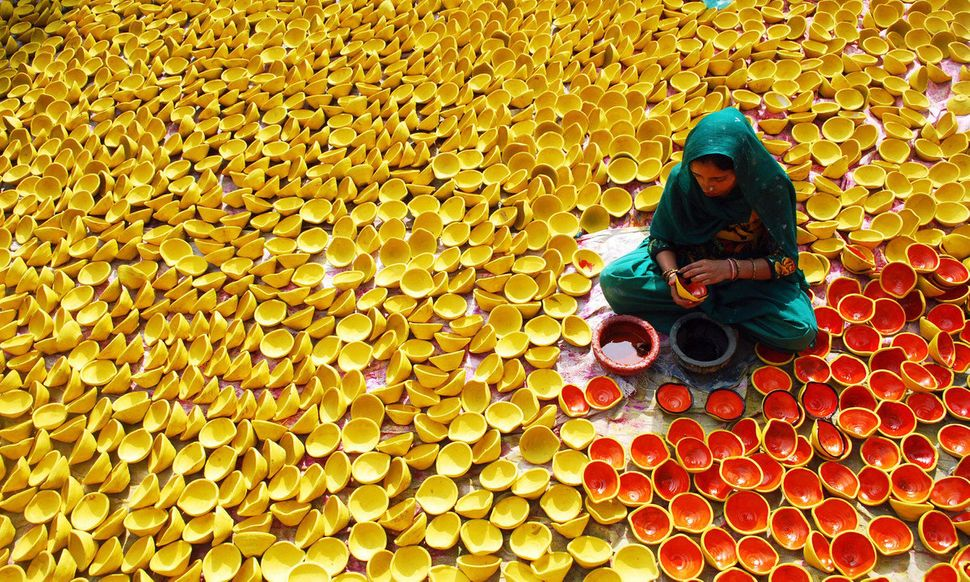 An Indian potter paints earthen lamps ahead of Diwali, or the Hindu festival of lights, in Amritsar, India, Wednesday, Oct. 3
