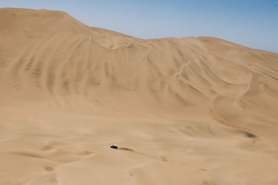 Mini driver Stephane Peterhansel and co-pilot Jean Paul Cottret, both of France, race through the dunes during the ninth stag