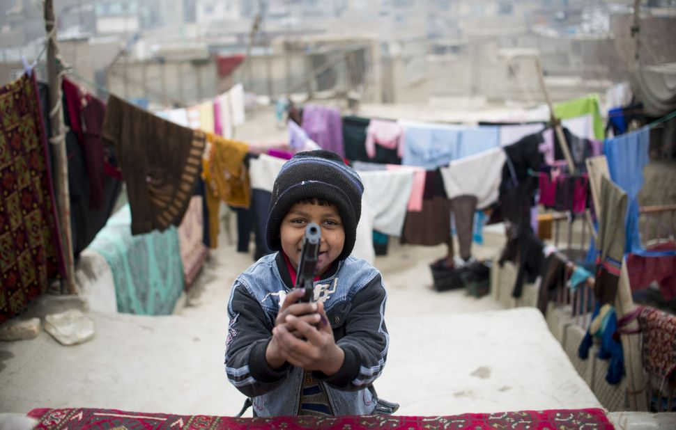 Nine year old Afghan boy, Zubair Ahmad plays with a plastic gun on a roof top in the old quarters of Kabul on January 16, 201