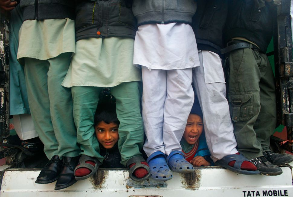 Nepalese Muslim boys peek out from a vehicle as they participate in a rally to mark Milad-un-Nabi, the festival that commemor