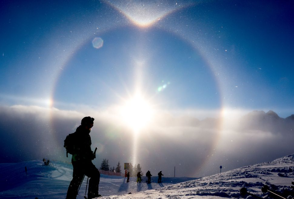 The sun creates a halo over skiers at Fellhorn on January 15, 2014 in Oberstdorf, Germany. Also called a nimbus or icebow, a