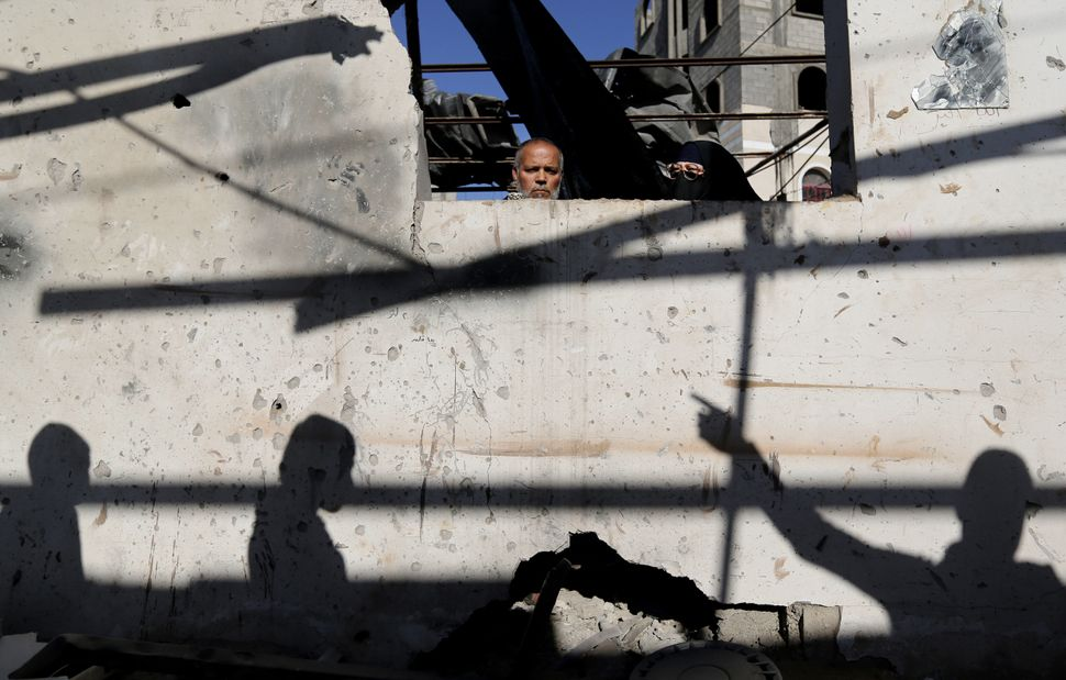 Palestinians inspect damages of their home after an Israeli airstrike in Gaza City, Thursday, Jan. 16, 2014. Israel's militar