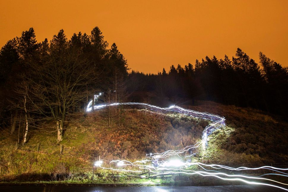 Light-trails illuminate from head torches worn by competitors taking part in the 'Marmot Dark Mountains' night-time adventure
