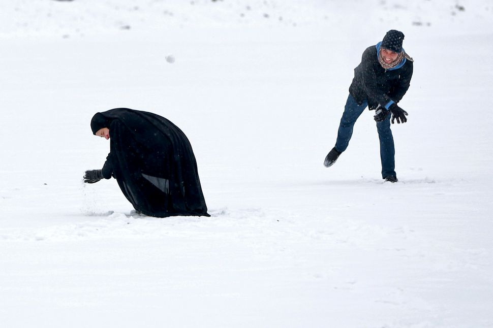 An Iranian man throws a snowball at his wife in Tehran, Iran, Tuesday, Feb. 4, 2014. Tehran and many parts of Iran were blank