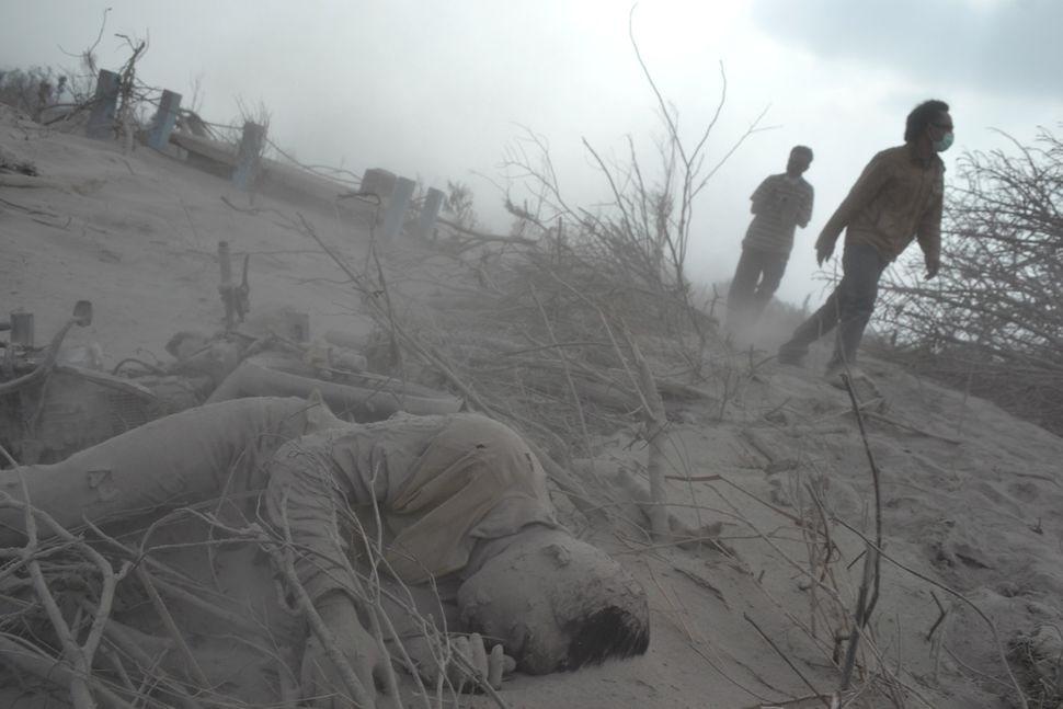 Rescuers arrive to recover the body of a victim covered in volcanic ash at a village in Karo district following eruptions of