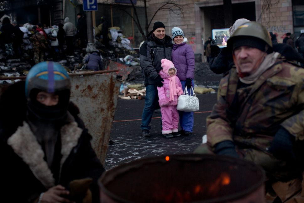 A family is photographed near to a barricade as opposition supporters warm themselves around the fire near Kiev's Independenc