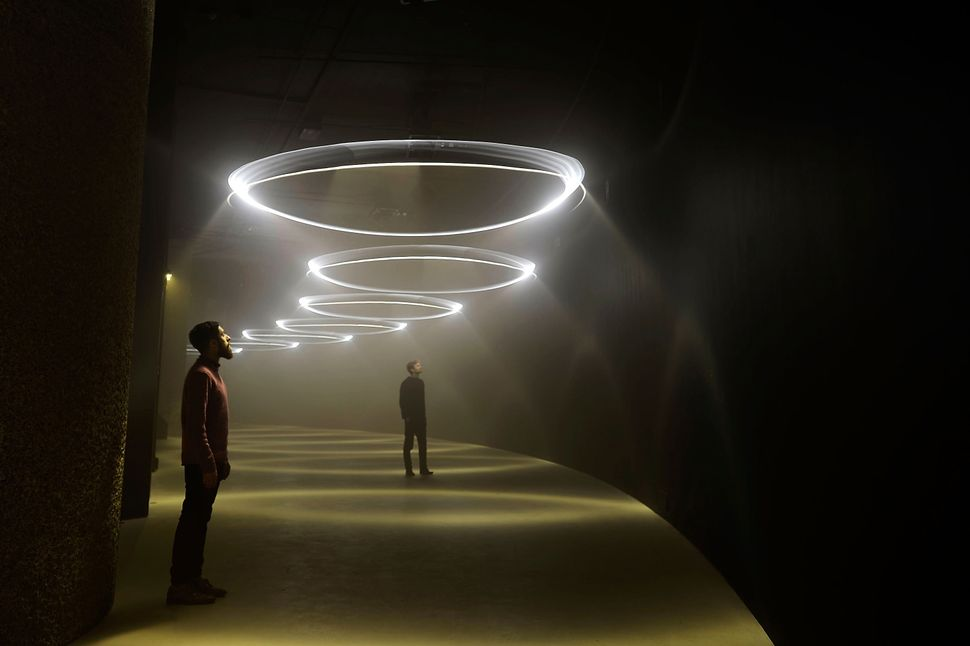 Visitors enjoy the 'United Visual Artists: Momentum' installation at The Curve at the Barbican Centre on February 12, 2014 in