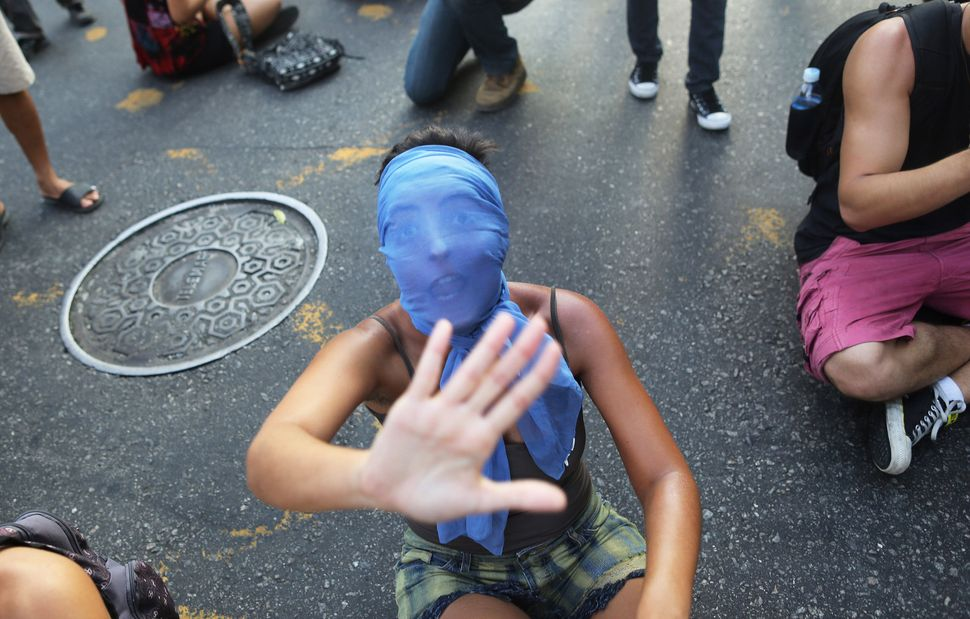 A masked girl shouts while sitting on the street, in protest against the increase on bus fares in Rio de Janeiro, Brazil, Mon