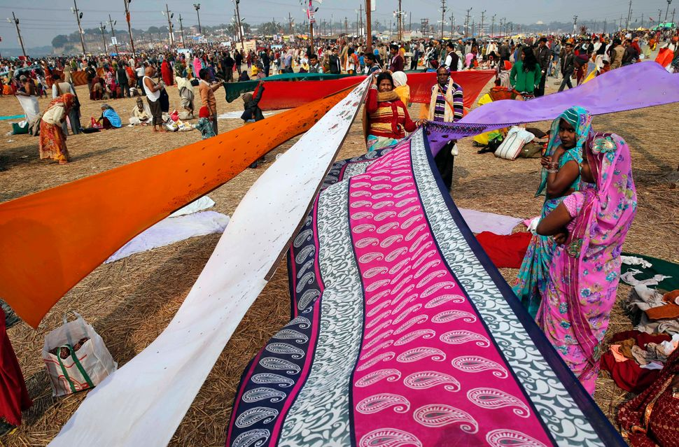 Indian women dry their saris after taking a dip at Sangam, the confluence of the Rivers Ganges, Yamuna and mythical Saraswati