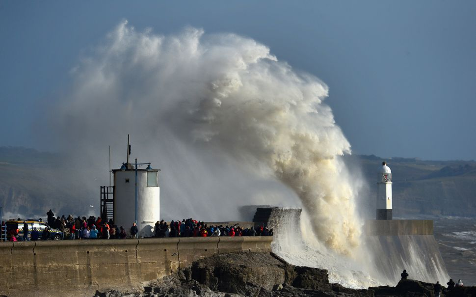 Waves break over the harbour wall during high tide as people watch on February 9, 2014 in Porthcawl, United Kingdom. (Stu For