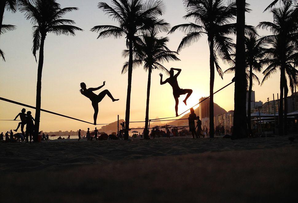 People practice slacklining on Copacabana Beach on February 8, 2014 in Rio de Janeiro, Brazil. Brazil is ramping up to host t