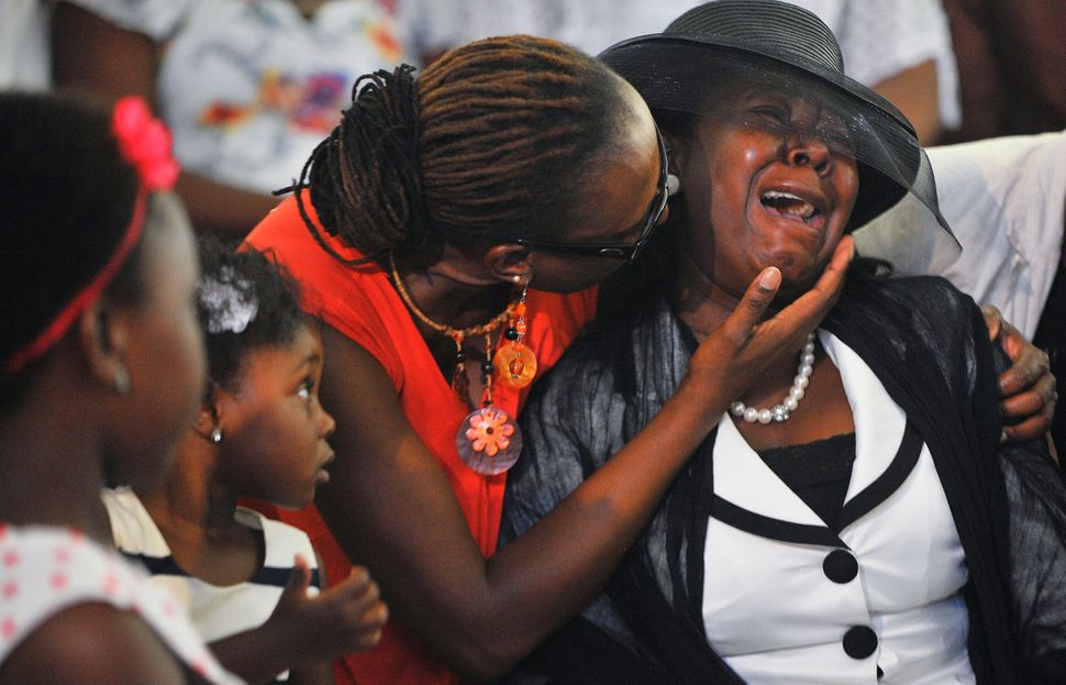 A family member weeps during a memorial service to honour the lives of mineworkers at Harmony's Doornkop gold mine, Gauteng,