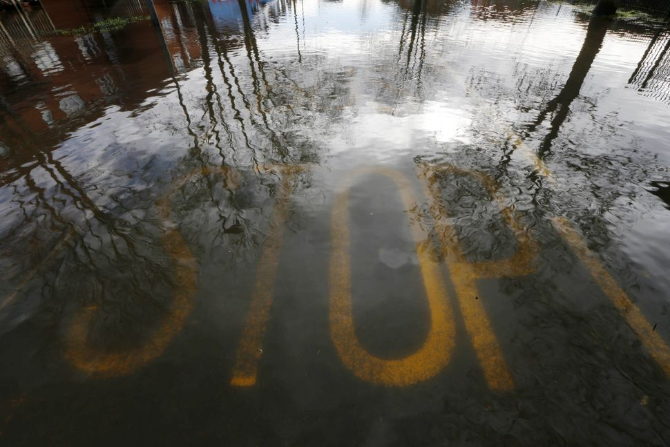 A warning stop sign is submerged in a flooded road in Egham, England, Thursday, Feb. 13, 2014. The River Thames has burst its
