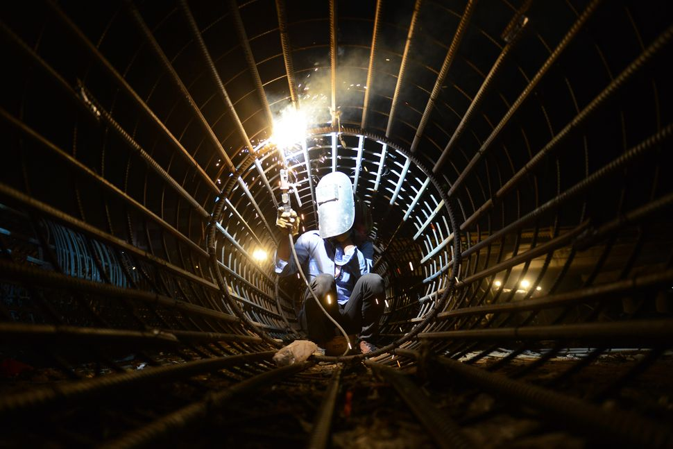 Nepalese worker Raju Tamang, 20, works on the iron frame of a pillar during a bridge expansion project in Kathmandu on Februa