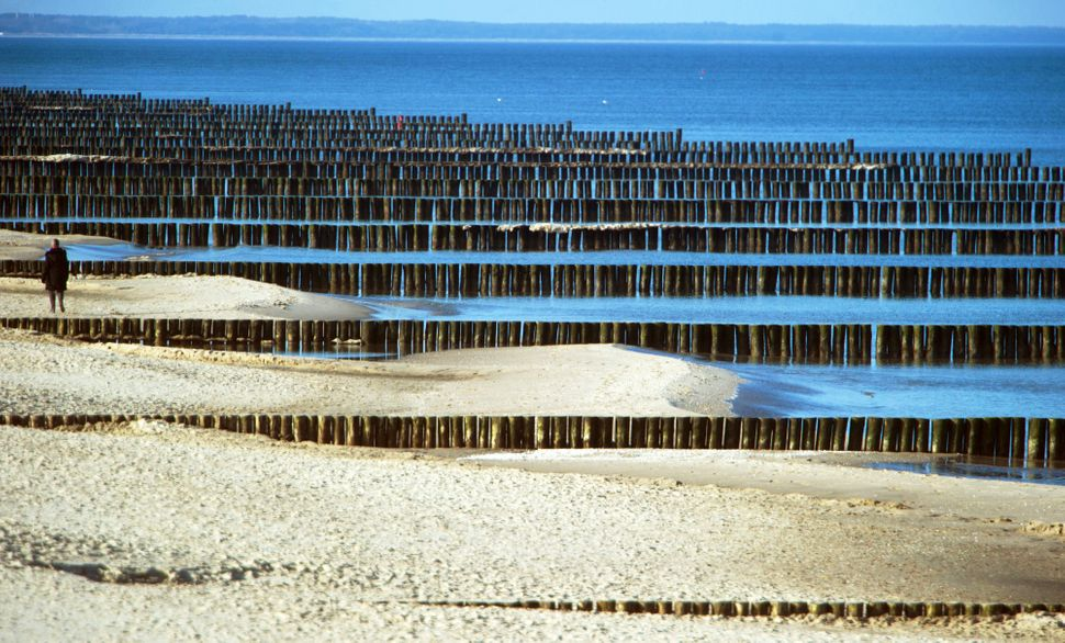 A person passes groynes near Koserow , Germany, on the Baltic Sea island of Usedom, Wednesday Feb. 12, 2014. Weather forecast