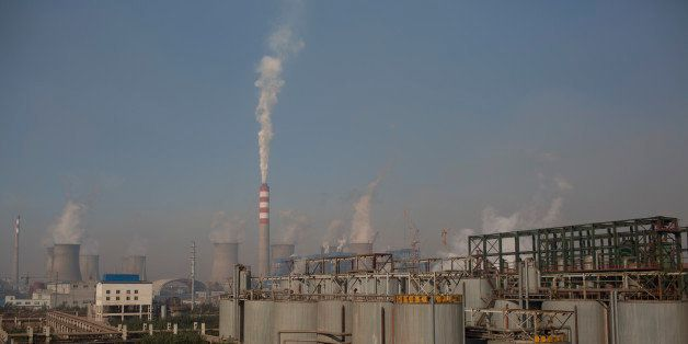 Vapor rises from cooling towers at a power plant, background, at the China Hongqiao Group Ltd. aluminum smelting facility in