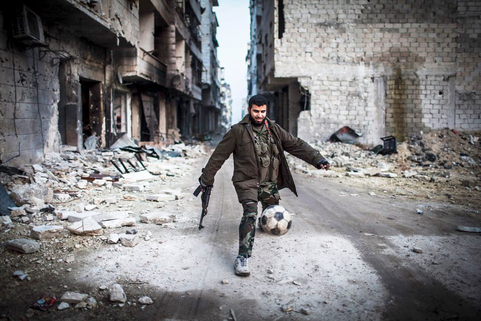 A Syrian rebel plays football in the Saif al-Dawlah neighborhood of Aleppo, Syria, Wednesday, Jan. 2, 2013. The United Nation