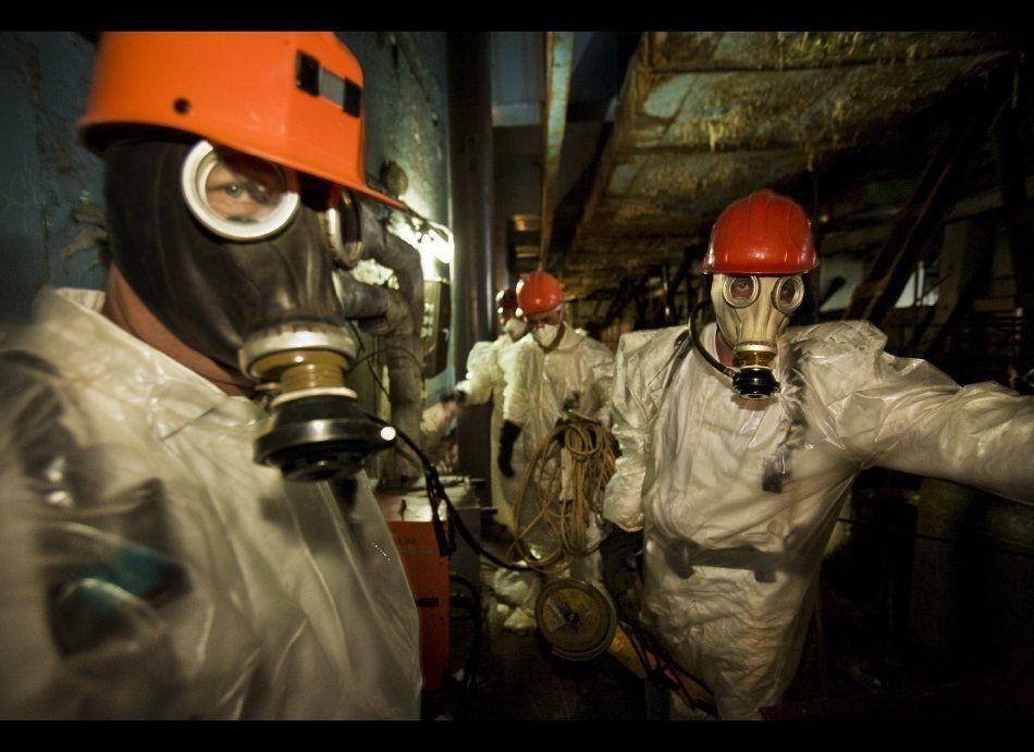 Enter caption for this slideWorkers wearing plastic suits and respirators for protection pause briefly on their way to drill