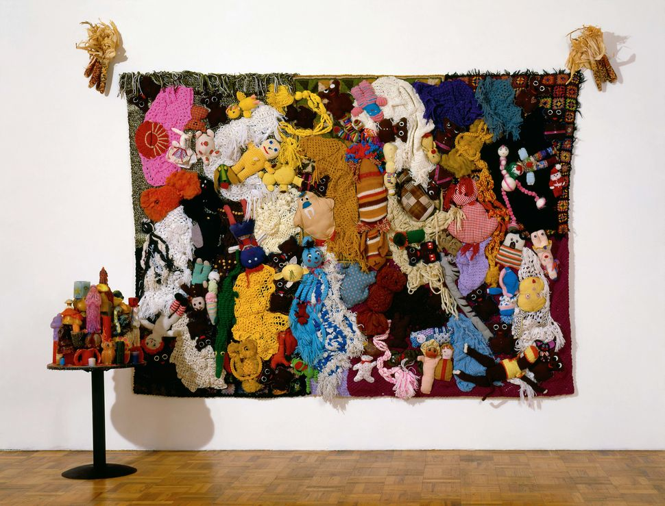 """This piece, also part of the """"Half a Man"""" project, weaves together used children's toys onto a wall hanging, resembling a nig"""