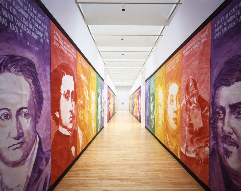 """""""Pay for Your Pleasure"""" consists of 42 colorful banners depicting poets, politicians and artists, lining the walls of a hallw"""