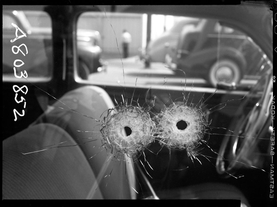 Detail of two bullet holes in car window Date: 10/10/1942