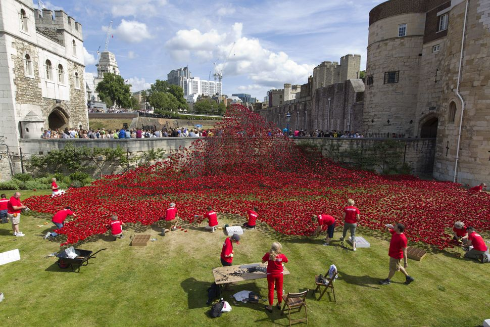 Volunteers install porcelain poppies as part of the art installation 'Blood Swept Lands and Seas of Red' by ceramic artist Pa