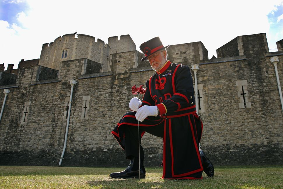 Crawford Butler, the longest serving Yeoman Warden at the Tower of London, poses with the first ceramic poppy to be 'planted'