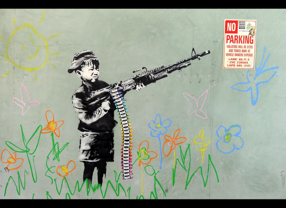 A graffiti attributed to secretive British artist Banksy depicting a child wielding a machine gun, in black and white surroun