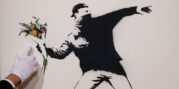 A Bonhams employee points at the colored detail of a spray paint work by urban artist Banksy at Bonhams auction house in Lond