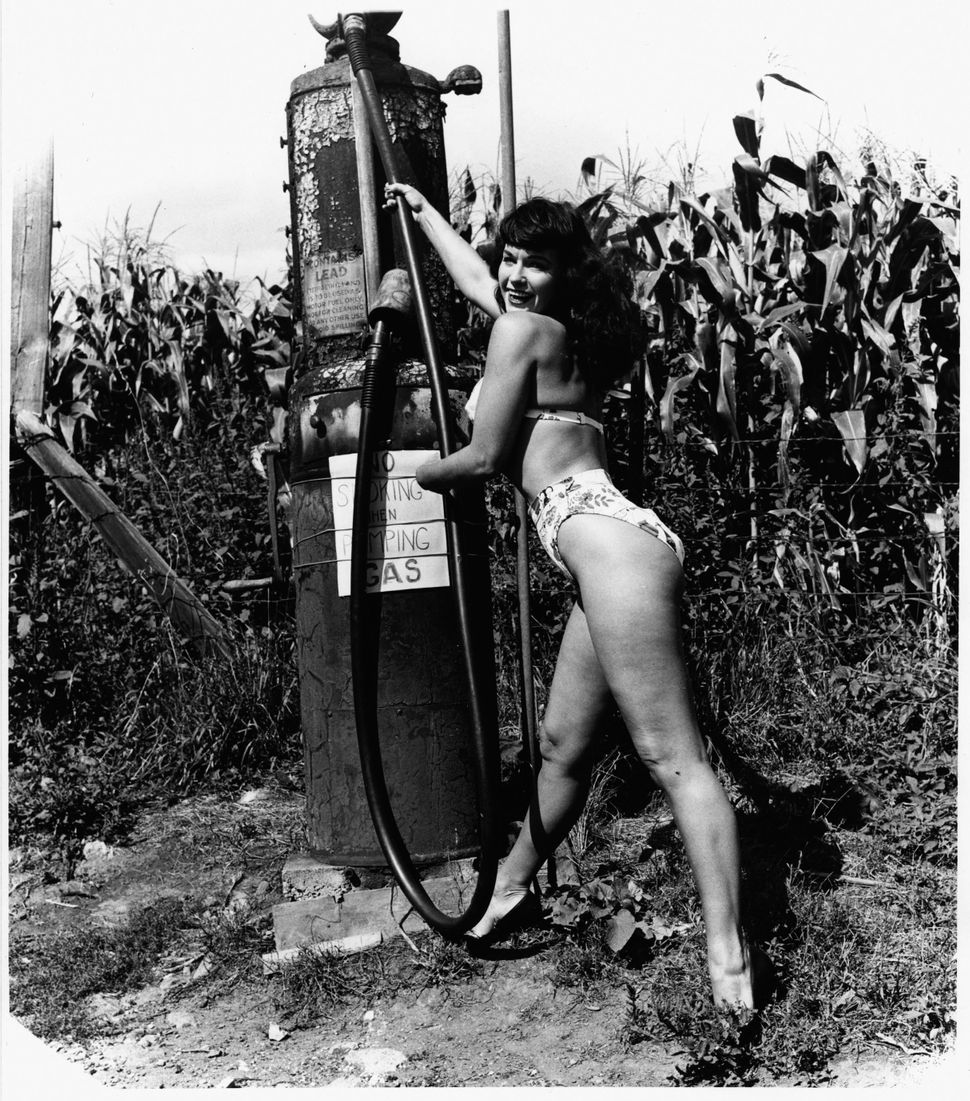 American pin-up model Bettie Page leans in and holds onto the hose of a gas pump as she smiles and wears high heels beside a