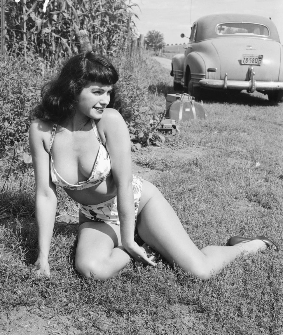 American pin-up Bettie Page, Playboy playmate of the month for January 1955, sunbathes in a country lane, New York state, 195