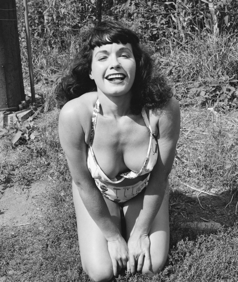 American pin-up Bettie Page, Playboy playmate of the month for January 1955 shows off her cleavage in a bikini, New York stat